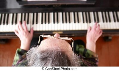 Senior woman in eyeglasses is playing the piano, top view