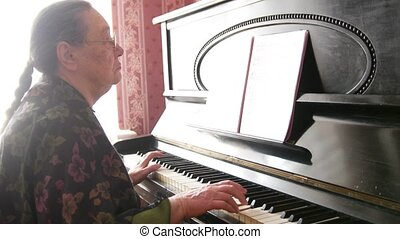 Senior woman in eyeglasses is playing the piano