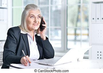 Senior woman in formal wear working in office - Beautiful...