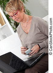 Senior woman in front of a laptop at home
