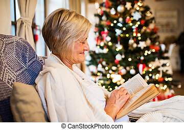Senior woman in front of Christmas tree