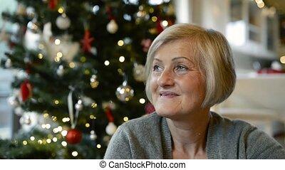 Senior woman in front of illuminated Christmas tree. -...