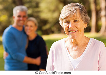 senior woman in front of middle aged son and daughter-in-law...
