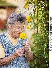 Senior woman in garden - Portrait of senior woman in apron ...