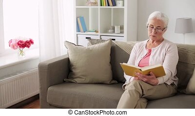 senior woman in glasses reading book at home - old age,...