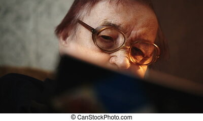 Dolly close-up shot of old woman in glasses reading a book at home