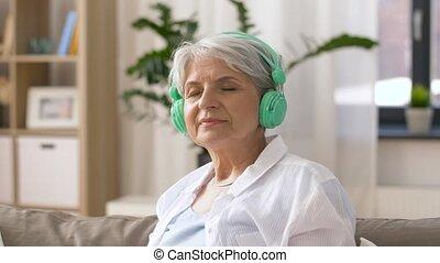 senior woman in headphones listening to music - technology,...