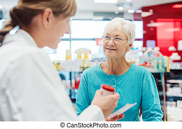 Senior woman in pharmacy talking to the chemist or pharmacist