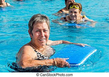 Senior woman in pool with kicking board.