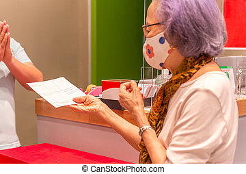 Senior woman in protective mask check a receipt in shopping store.