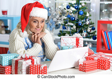 Senior woman in Santa hat with presents using laptop