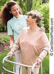 Senior woman in the garden - Senior woman with walking frame...