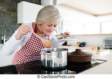 Senior woman in the kitchen cooking, mixing food in a pot.