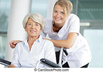 senior woman in wheelchair and a nurse