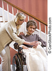 Senior woman in wheelchair at home with nurse