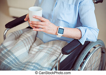 Senior woman in wheelchair holding cup