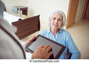 Senior woman in wheelchair with doctor