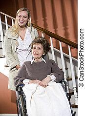 Senior woman in wheelchair with nurse helping