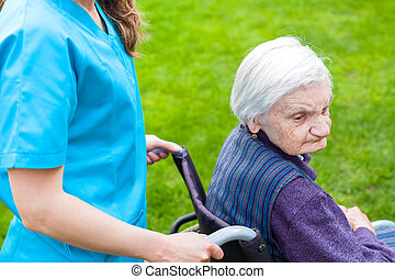 Senior woman in wheelchair with nurse