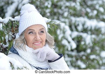 Senior woman in winter park - Portrait of smiling senior...