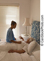 Senior woman interacting with female doctor in bedroom