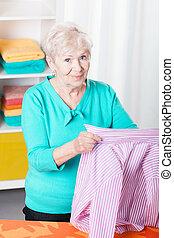 Senior woman ironing shirt