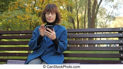 Senior woman is chatting with friends in a smartphone while sitting in a cozy park. Happy old woman looking at screen on smartphone. Elderly woman uses wireless internet connection in slow motion.