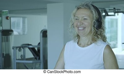 senior woman is engaged on a treadmill in the gym. blond female listens to music with headphones on the treadmill