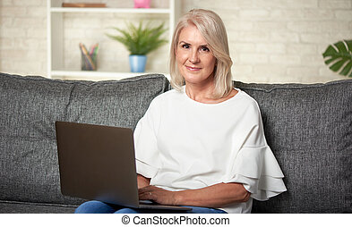 Senior woman is sitting on sofa with laptop computer at home