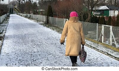 Senior woman is walking along the path in the allotments