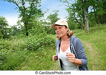 Senior woman jogging in forest