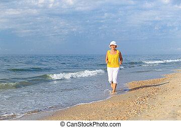 senior woman jogging on sea beach