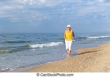 senior woman jogging on sea beach