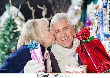 Senior Woman Kissing Man With Christmas Presents