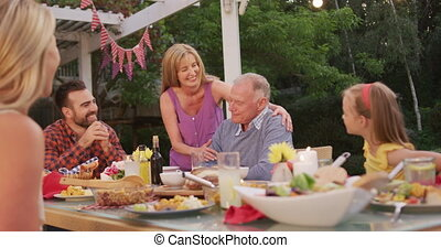 Senior woman kissing senior man while having lunch outdoors...
