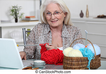 Senior woman knitting in front of her laptop computer