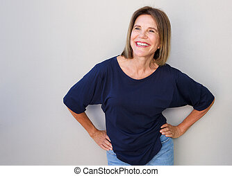 senior woman laughing against gray background