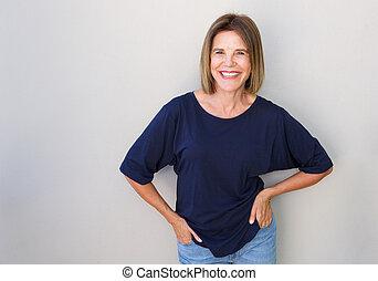 Senior woman laughing against gray wall