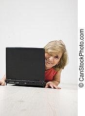 Senior woman laughing behind a laptop