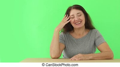 Senior woman laughing while sitting at table