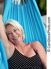 Senior woman laying on a hammock