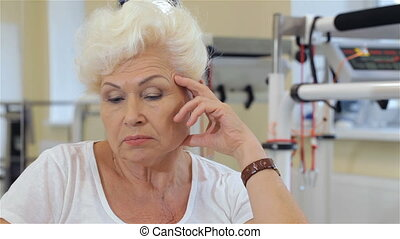 Senior woman leans her head on her hand