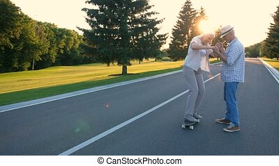 Senior woman learning to skateboard with husband