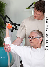 Senior woman lifting dumbbell with fitness coach