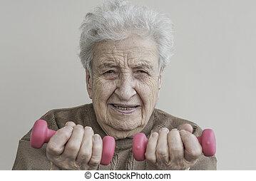Senior woman lifting dumbbells