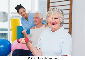 Senior woman lifting dumbbells while sitting with man and instru