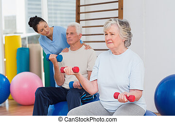 Senior woman lifting dumbbells with man and trainer at gym