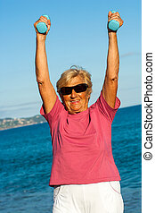 Senior woman lifting weights outdoors.