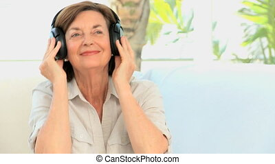 Senior woman listening music at home