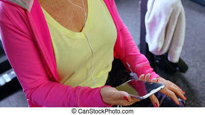 Senior woman listening music on mobile phone in fitness...